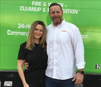 Woman and man in front of green truck